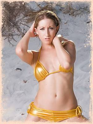 Aubrey plays in the sand in a gold bikini