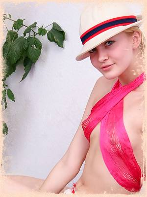 Radiant blond girl poses with just her hat on