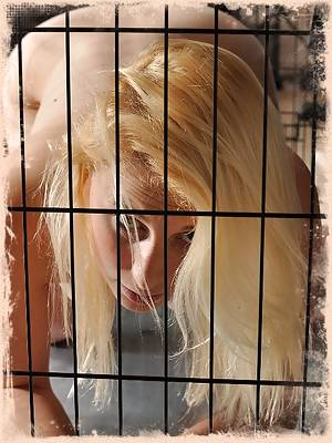 Blonde naked busty babe is tied up in a dog cage